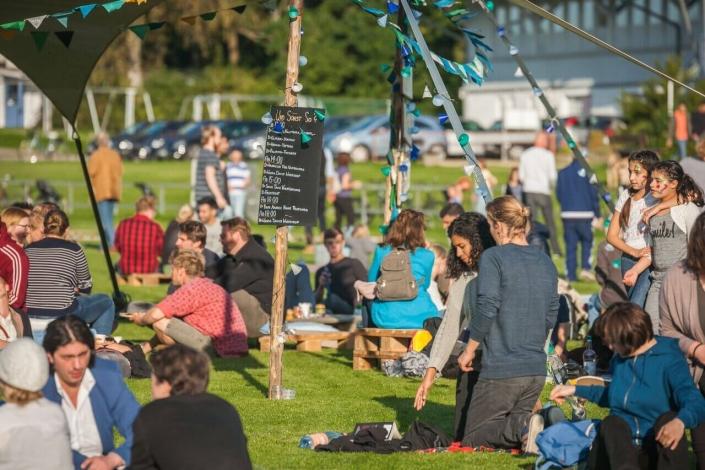 Menschen sitzen im Park beim kulturgrenzenlos Festival