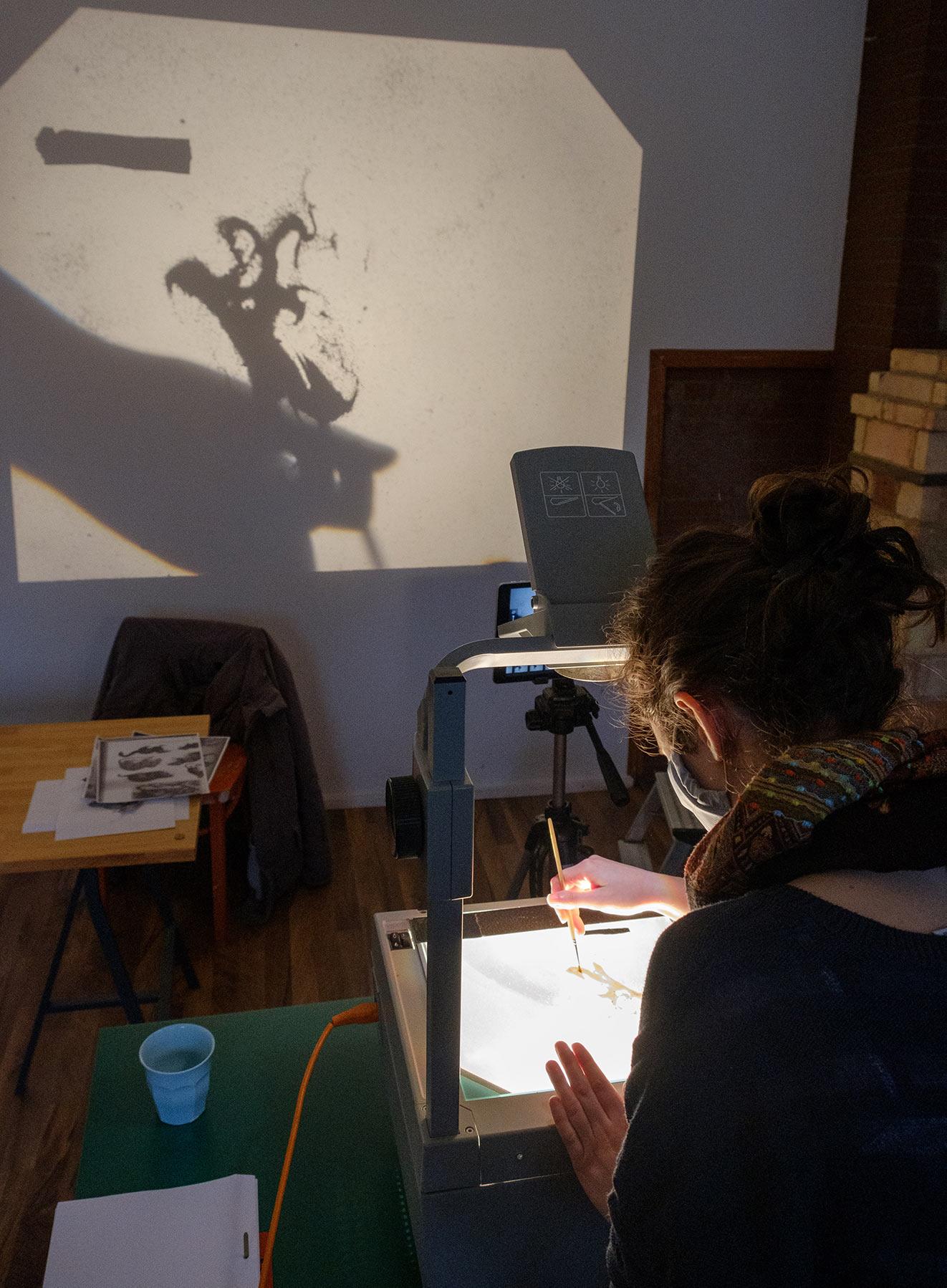 Auf Overheadprojekor wird mit Sand gemalt. Formen werden an Wand projeziert.
